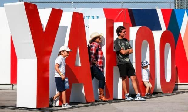 Visitors pose for photos at the Calgary Stampede. The event was smaller this year due to COVID-19 precautions, and about half as many visitors attended.  (Jeff McIntosh/The Canadian Press - image credit)