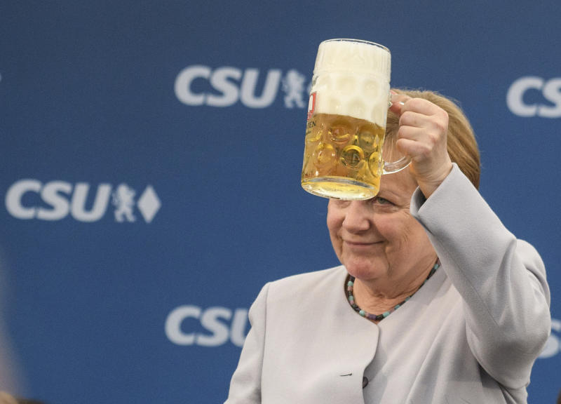 German Chancellor Angela Merkel lifts a glass of beer during an election campaign of her Christian Democratic Union, CDU, and the Christian Social Union, CSU, in Munich, southern Germany, Sunday, May 28, 2017. A poll of German voters shows Chancellor Merkel's conservative bloc's lead widening as the main challenger Social Democrats continue to lose support. (Matthias Balk/dpa via AP)