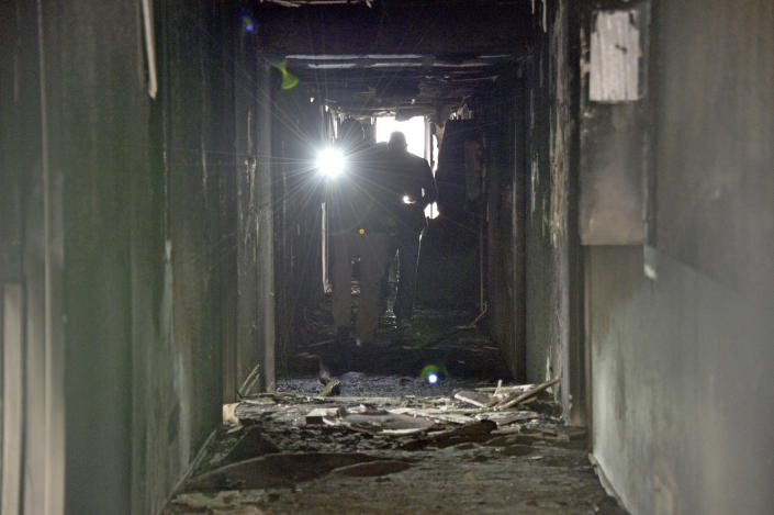 Investigators walk through an interior corridor after a fire at a three-story apartment complex early Saturday, Dec. 21, 2019 in Las Vegas. The fire was in first-floor unit of the Alpine Motel Apartments and its cause was under investigation, the department said. Authorities say multiple fatalities were reported and many more were injured. (AP Photo/David Becker)