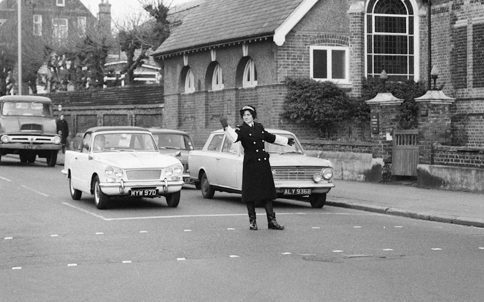 Britain's first Traffic Warden to control traffic as opposed to booking cars for parking offences, Mrs Joyce Roffey, on point duty at a busy crossroads in Croydon, Surrey, the junction of Park Lane and Coombe Road, 2nd January 1967. (Photo by Eric Harlow/Mirrorpix/Getty Images)  - Getty