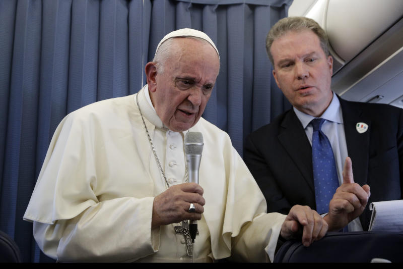 FILE - In this Sunday, Aug. 26, 2018 file photo, Pope Francis, flanked by Vatican spokesperson Greg Burke, listens to a journalist's question during a press conference aboard of the flight to Rome at the end of his two-day visit to Ireland. The Vatican spokesman, Greg Burke, and his deputy resigned suddenly Monday, Dec. 31, 2018 amid an overhaul of the Vatican's communications operations that coincides with a troubled period in Pope Francis' papacy. In a tweet, Burke said he and his deputy, Paloma Garcia Ovejero, had resigned effective Jan. 1. (AP Photo/Gregorio Borgia, Pool)