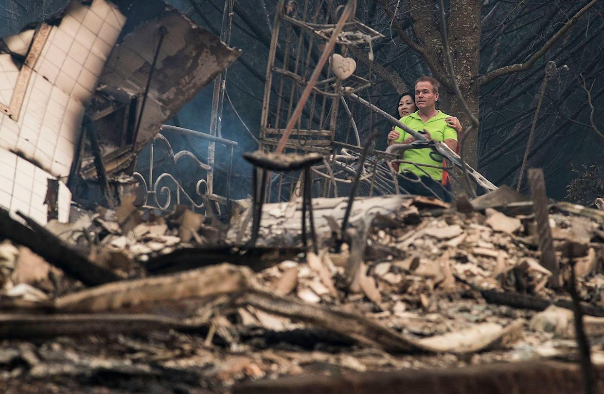 Mark Williams, right, and friend Norina Wong, left, look over the destruction in their friends' neighborhood off Fountaingrove Parkway near the Hilltop in Santa Rosa.