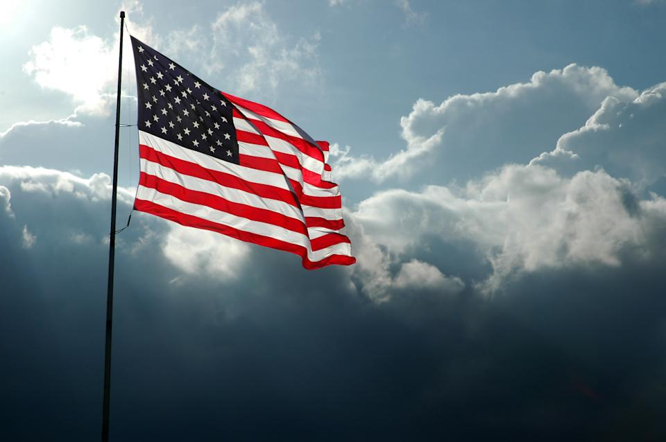 Back-lit American flag waving in the wind with a storm front moving in