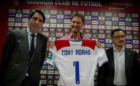 Former Arsenal and England captain Tony Adams (C) holds Granada's jersey as he is flanked by the club's vice-president Kangning Wang (R) and the club's board member Ignacio Cuerva, after being presented as the new head coach in Granada, Spain April 11, 2017. REUTERS/Pepe Marin
