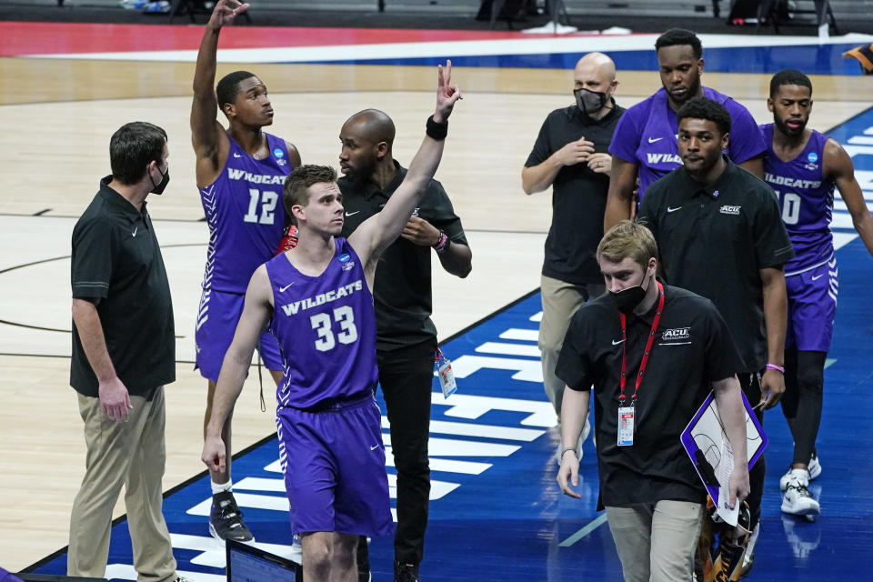 Abilene Christian's Mahki Morris (12) and Paul Hiepler (33) wave to fans as they leave the court after their 67-47 loss to UCLA in a college basketball game in the second round of the NCAA tournament at Bankers Life Fieldhouse in Indianapolis Monday, March 22, 2021. (AP Photo/Mark Humphrey)