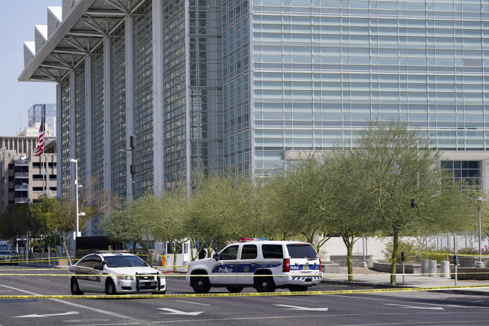 Police cars close off a street outside the Sandra Day O'Connor U.S. Courthouse in Phoenix, on Tuesday, Sept. 15, 2020. A drive-by shooting wounded a federal court security officer Tuesday outside the courthouse in downtown Phoenix, authorities said. The officer was taken to a hospital and is expected to recover, according to city police and the FBI, which is investigating. (AP Photo/Ross D. Franklin)