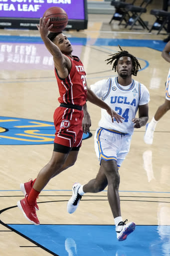 Utah guard Alfonso Plummer, left, grabs a high pass over UCLA forward Jalen Hill during the first half of an NCAA college basketball game Thursday, Dec. 31, 2020, in Los Angeles. (AP Photo/Marcio Jose Sanchez)