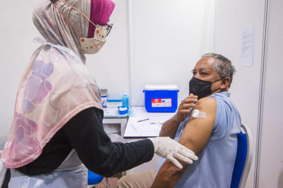 People receive their vaccine at the Covid-19 vaccination centre at the Mines International Exhibition and Convention Centre, Seri Kembangan, June 17, 2021. — Picture by Shafwan Zaidon