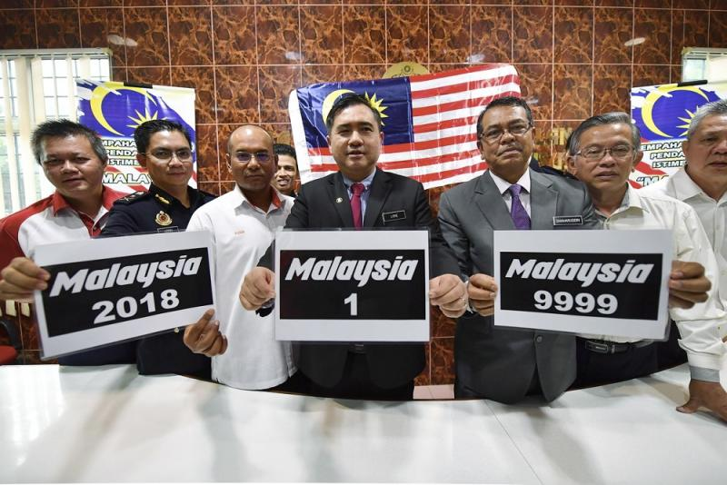 Transport Minister Anthony Loke (fourth left) shows the special number plates during a press conference in Seremban August 1, 2018. — Bernama pic