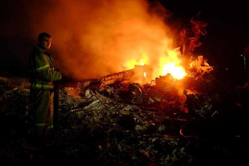 A firefighter stands as flames burst amongst the wreckage of the Malaysian airliner carrying 298 people from Amsterdam to Kuala Lumpur after it crashed, near the town of Shaktarsk, in rebel-held east Ukraine, on July 17, 2014 (AFP Photo/Dominique Faget)