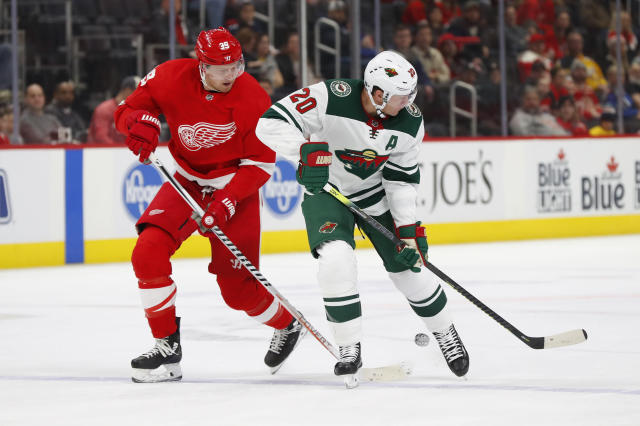 Detroit Red Wings right wing Anthony Mantha (39) and Minnesota Wild defenseman Ryan Suter (20) battle for the puck in the second period of an NHL hockey game Thursday, Feb. 27, 2020, in Detroit. (AP Photo/Paul Sancya)