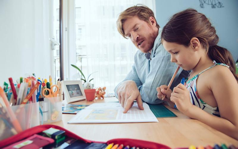 Father helping girl doing her schoolwork at home - Getty Images Contributor