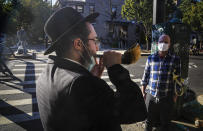 FILE - In this Sept. 20, 2020, file photo, an Orthodox Jewish man blows the Shofar after a brief prayer with a passerby in New York. Amid a new surge of COVID-19 in New York's Orthodox Jewish communities, many residents are reviving health measures that some had abandoned over the summer – social distancing, wearing masks. For many, there's also a return of anger: They feel the city is singling them out for criticism that other groups avoid. (AP Photo/Bebeto Matthews, File)