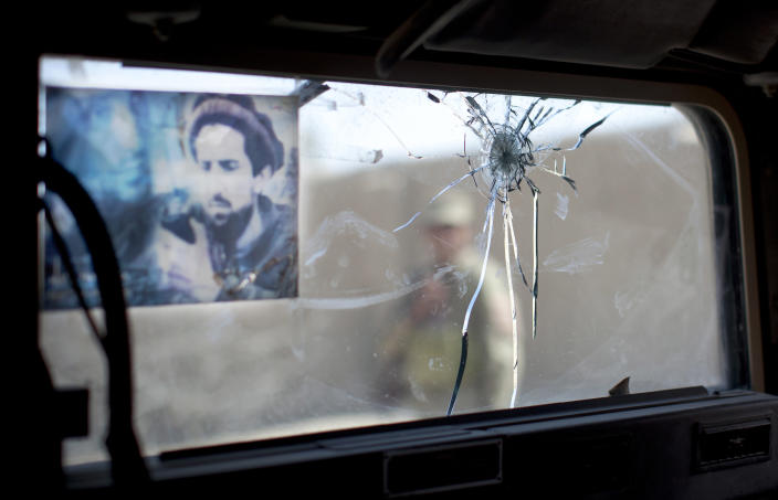 An Afghan National policeman is seen through a windscreen of an armored vehicle shattered by a single bullet in Lashkar Gah, Helmand Province, Afghanistan, Thursday, Oct 18, 2012. The police have decorated the window with a picture Ahmad Shah Massoud, an Afghan leader killed Sept 9, 2009, by an Al Qaida suicide bomber. (AP Photo/Anja Niedringhaus)