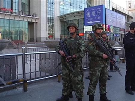 Armed police officers stand guard at the South Railway Station, where three people were killed and 79 wounded in a bomb and knife attack, in Urumqi, in this still image taken from CCTV video shot April 30, 2014. REUTERS/CCTV/Handout via Reuters