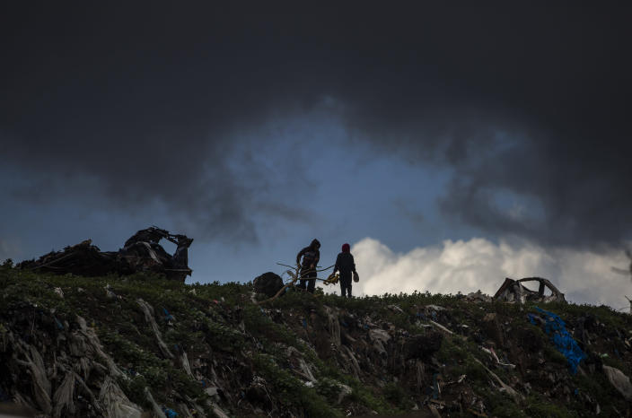 Two Palestinian boys play on top of piles of garbage on a rainy day in a poor neighbourhood of Khan Younis, in the southern Gaza Strip, Wednesday, Jan. 20, 2021. (AP Photo/Khalil Hamra)