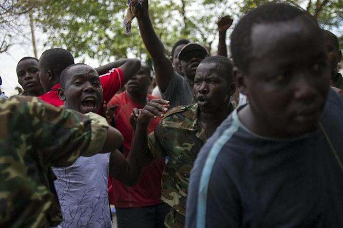 """Burundian soldiers hold back civilians after they caught a man accused of being an """"Imbonerakure"""", a member of the ruling CNDD-FDD party's youth wing, on May 9, 2015 (AFP Photo/Phil Moore)"""