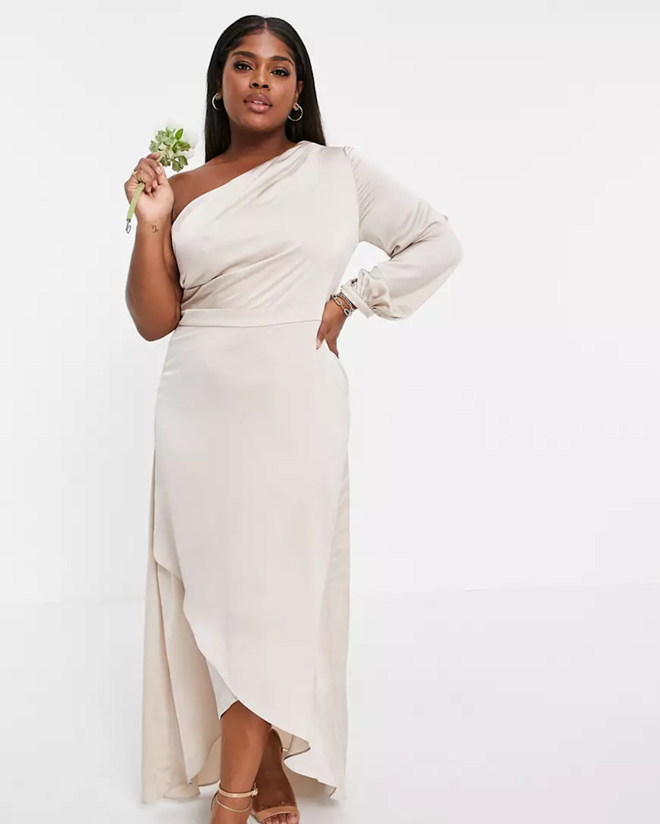 """With a pale Champagne hue, this one-shoulder maxi is the perfect cheap bridesmaid dress for a neutral color scheme. $106, ASOS. <a href=""""https://www.asos.com/us/tfnc-plus/tfnc-plus-bridesmaid-satin-one-shoulder-long-sleeve-maxi-dress-in-mink/prd/23487096"""" rel=""""nofollow noopener"""" target=""""_blank"""" data-ylk=""""slk:Get it now!"""" class=""""link rapid-noclick-resp"""">Get it now!</a>"""