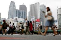 FILE PHOTO: People cross a street in front of high-rise buildings in the Shinjuku district in Tokyo