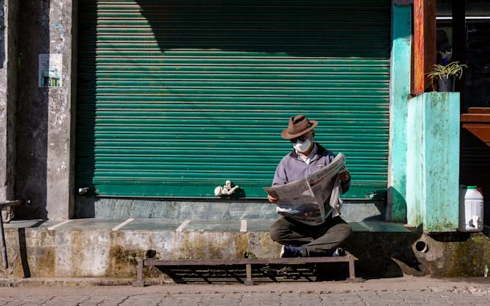 A man wearing a mask to protect reads a newspaper in front of a closed shop in Dharmsala, India - AP