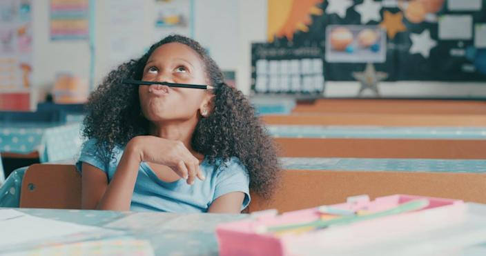 A young girl balances a pencil on her upper lip in class.