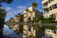 A bicyclist makes his way down East Battery as a king tide rolls into the historic Battery causing flooding in Charleston, S.C. Sunday, Nov. 15, 2020. Charleston has remained relatively unscathed this hurricane season. That means more time to mull a $1.75 billion proposal by the Army Corps of Engineers that features a sea wall along the city's peninsula to protect it from deadly storm surge during hurricanes. (AP Photo/Mic Smith)