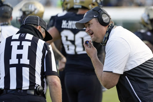 Central Florida head coach Josh Heupel, right, has words with head linesman Jim Casey, left, during the first half of an NCAA college football game against Cincinnati, Saturday, Nov. 21, 2020, in Orlando, Fla. (AP Photo/John Raoux)