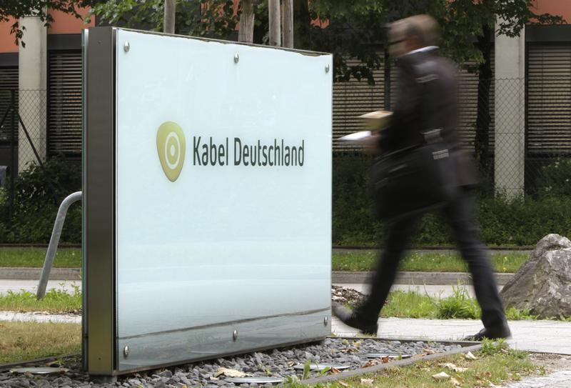 A man passes the company logo of German cable television group Kabel Deutschland in Unterfoehring