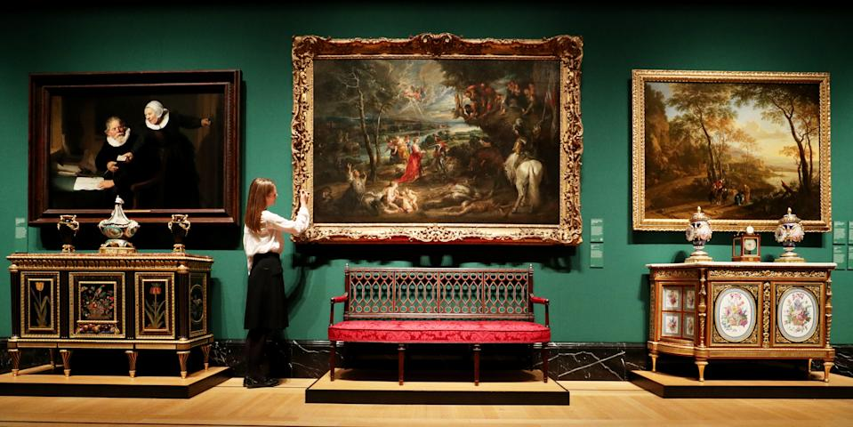 A Royal Collection staff member dusts the frame of Landscape with Saint George and the Dragon by Sir Peter Paul Rubens during a preview of the Royal Collection's George IV: Art & Spectacle exhibition in The Queen's Gallery at Buckingham Palace in London. (Photo by Jonathan Brady/PA Images via Getty Images)