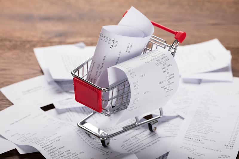 Close-up Of A Shopping Cart With Bunch Of Receipts On Wooden Desk