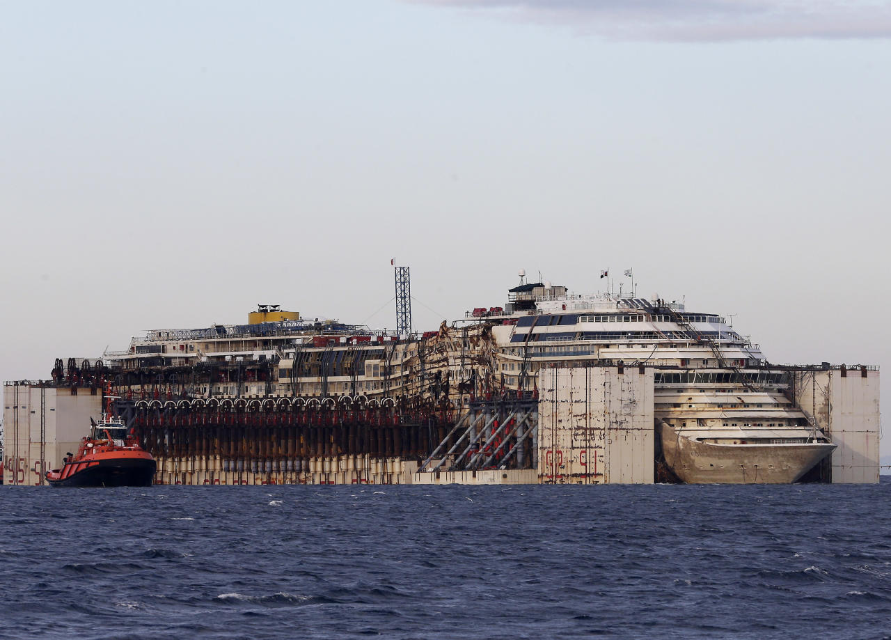 The wreck of the Costa Concordia cruise ship is towed by tugboats towards Genoa's harbor, Italy, Sunday, July 27, 2014. The shipwrecked Costa Concordia cruise liner has completed its final journey. Pulled by tugboats and nudged by brisk winds, the wreck was eased Sunday into Genoa's port — where it will be scrapped. The luxury liner struck a reef when its captain sailed too close to Giglio Island off Tuscany's coast Jan. 13, 2012, and capsized, killing 32 people. A spectacular operation set the wreck upright in September 2013. On Wednesday, tugboats began the five-day journey to Genoa, headquarters of ship owner Costa Crociere Spa. The wreck will be searched in hopes of finding the remains of an Indian waiter, the only body never found. Ship captain Francesco Schettino is being tried for alleged manslaughter, causing the shipwreck and abandoning the boat with many passengers and crew still aboard. (AP Photo/Antonio Calanni)