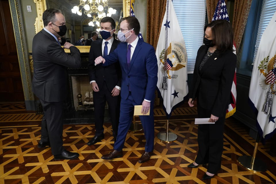 Pete Buttigieg, second left, looks on after being sworn in as Transportation Secretary by Vice President Kamala Harris, right, as Chasten Buttigief, second right, and Doug Emhoff, left, elbow bump, in the Old Executive Office Building in the White House complex in Washington, Wednesday, Feb. 3, 2021. (AP Photo/Andrew Harnik)