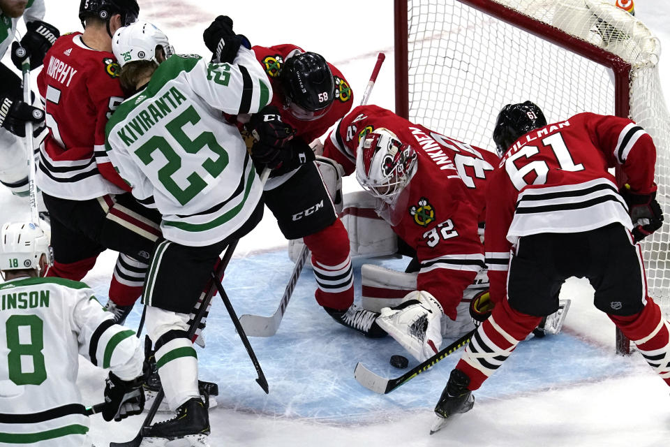 Chicago Blackhawks goaltender Kevin Lankinen (32) makes a save on a shot as Dallas Stars left wing Joel Kiviranta (25) battles for the puck against Chicago Blackhawks defenseman Connor Murphy (5) and right wing MacKenzie Entwistle (58) during the first period of an NHL hockey game in Chicago, Sunday, May 9, 2021. (AP Photo/Nam Y. Huh)