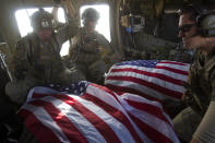 FILE - In this Oct. 10, 2010 file photo, U.S. Air Force pararescue members ride in the back of their medevac helicopter with the American flag draped over bodies of U.S. soldiers who were killed in a roadside bomb attack in Afghanistan's Kandahar province. (AP Photo/David Guttenfelder, File)