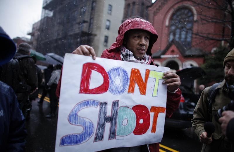 A man holds a banner during the funeral service of Akai Gurley, outside the Brown Memorial Baptist Church on December 6, 2014 in the Brooklyn borough of New York (AFP Photo/Kena Betancur)