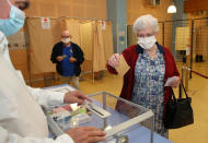 A woman casts a vote at a voting center during the second round of the municipal elections, in Saint Pee sur Nivelle, southwestern France, Sunday, 28, June, 2020. France is holding the second round of municipal elections in 5,000 towns and cities Sunday that were postponed due to the country's coronavirus outbreak. (AP Photo/Bob Edme)