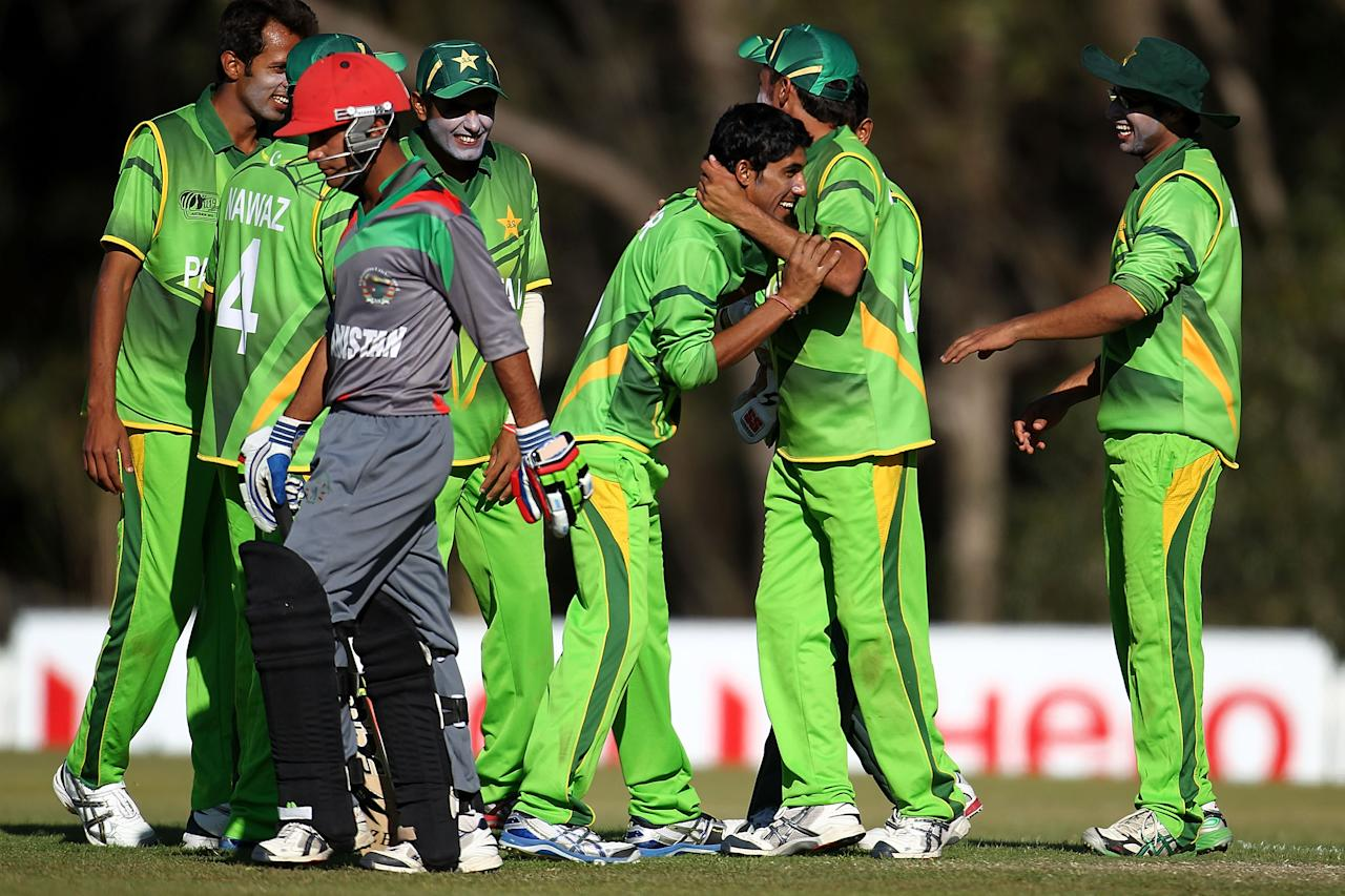 SUNSHINE COAST, AUSTRALIA - AUGUST 11:  Umar Waheed of Pakistan (C) is congratualted by his team mates after bowling out Nasir Jamal (L) of Afghanistan during the ICC U19 Cricket World Cup 2012 match between Pakistan and Afghanistan at John Blanck Oval on August 11, 2012 in Sunshine Coast, Australia.  (Photo by Graham Denholm-ICC/Getty Images)