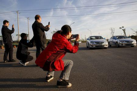 Visitors take pictures of Changan Automobile's self-driving cars, which are manually driven, as they complete a test drive from Chongqing to Beijing to arrive at Changan Automobile's Beijing headquarters, China, April 16, 2016. REUTERS/Kim Kyung-Hoon