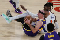Los Angeles Lakers guard Alex Caruso (4) controls the ball from the floor against New York Knicks center Nerlens Noel (3) during the first quarter of a basketball game Tuesday, May 11, 2021, in Los Angeles. (AP Photo/Ashley Landis)