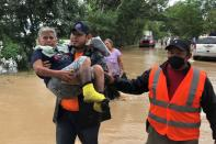 Members of the Honduras Permanent Contingencies Commission (COPECO) rescue a woman from her flooded home after the passage of Storm Eta, in El Progreso