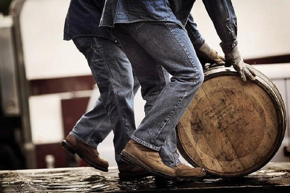 Two people in jeans rolling a wooden barrel.
