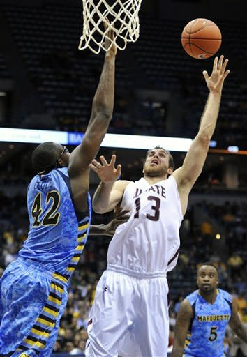Marquette's Chris Otule (42) tries to block the shot of Colgate's Murphy Burnatowski (13) during the second half of an NCAA college basketball game, Sunday, Nov. 11, 2012, in Milwaukee. (AP Photo/Jim Prisching)