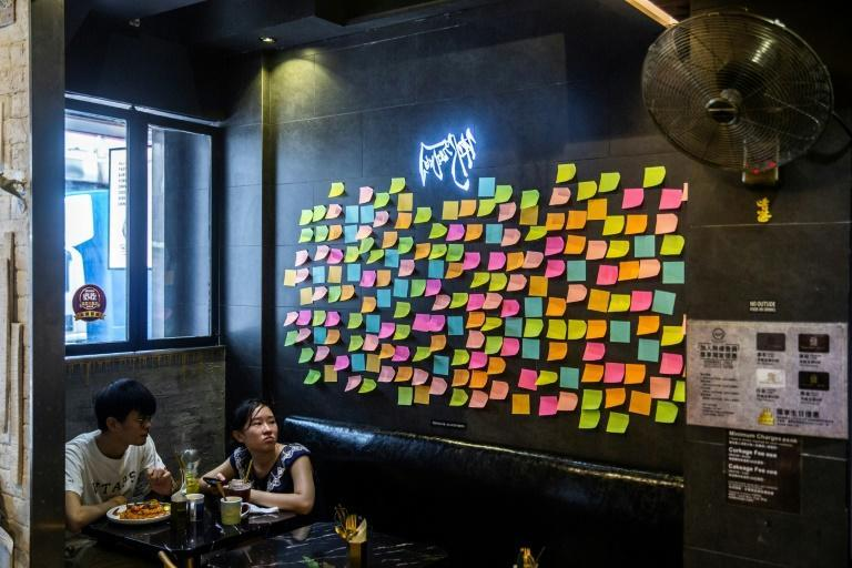 """Customers sit near notes deliberately left blank on a """"Lennon Wall"""" inside a pro-democracy restaurant in Hong Kong"""