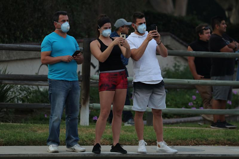 Residents use their phones to record firefighters in Orange, California.