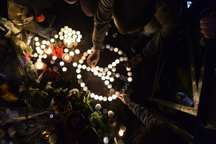 """People form the """"Pray for Paris"""" symbol with candles during a tribute at a makeshift memorial for the victims of a series of deadly attacks in Paris, near the """"Belle Equipe"""" cafe on Rue de Charonne in Paris on November 20, 2015 (AFP Photo/Alain Jocard)"""