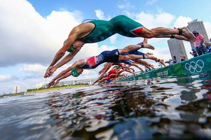 <p>Athletes compete in the men's individual triathlon competition during the Tokyo 2020 Olympic Games at the Odaiba Marine Park in Tokyo on July 26, 2021. (Photo by ANTONIO BRONIC / various sources / AFP)</p>