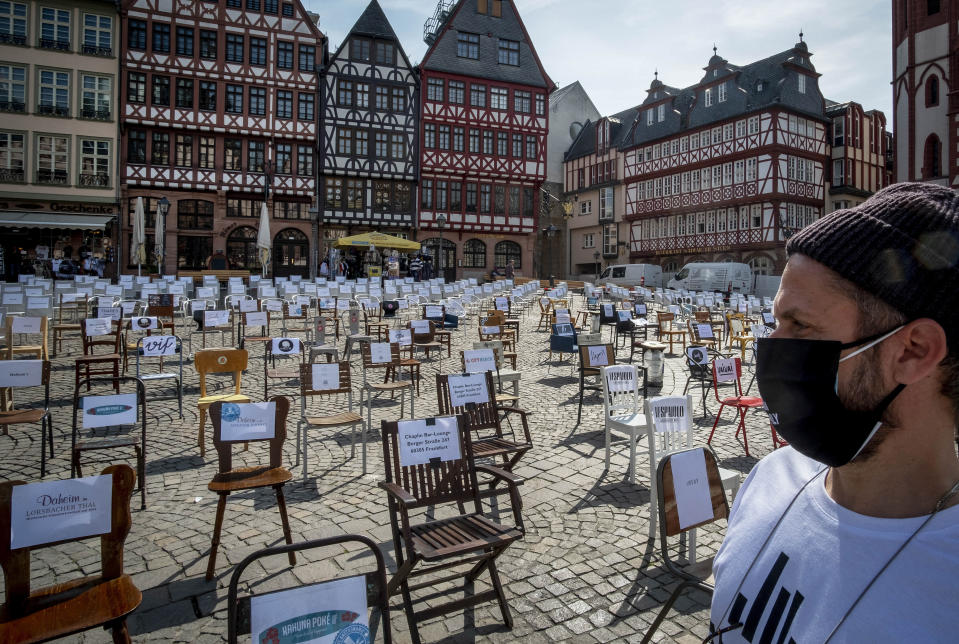 FILE - In this April 24, 2020 file photo, a man with a face mask watches empty chairs with names of bars and restaurants on the Roemerberg square in Frankfurt, Germany. More than 50,000 people have died after contracting COVID-19 in Germany, a number that has risen swiftly over recent weeks as the country has struggled to bring down infection figures. (AP Photo/Michael Probst, File)