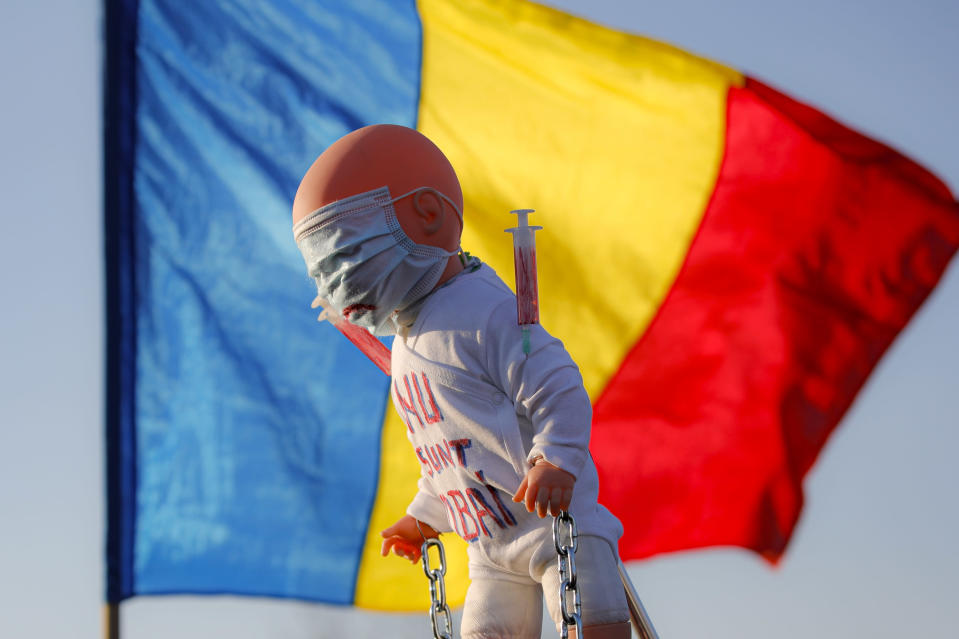 """Anti-vaccination protesters hold a doll with """"I don't want to be a lab rat"""" written on it backdropped by a Romanian national flag, during a rally outside the parliament building in Bucharest, Romania, Sunday, March 7, 2021. Some thousands of anti-vaccination protestors from across Romania converged outside the parliament building protesting against government pandemic control measures as authorities announced new restrictions amid a rise of COVID-19 infections. (AP Photo/Vadim Ghirda)"""
