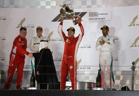 Formula 1 F1 - Bahrain Grand Prix - Bahrain International Circuit, Sakhir, Bahrain - April 8, 2018   Ferrari's Sebastian Vettel celebrates with the trophy as Mercedes' Lewis Hamilton and Mercedes' Valtteri Bottas look on after the race   REUTERS/Ahmed Jadallah