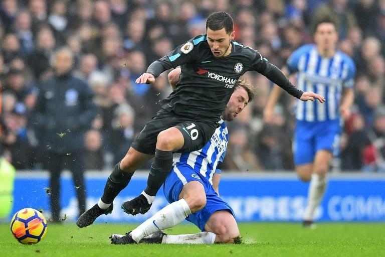 Chelsea midfielder Eden Hazard (left) rides a tackle by Brighton's Dale Stephens during their English Premier League match in Brighton on January 20, 2018